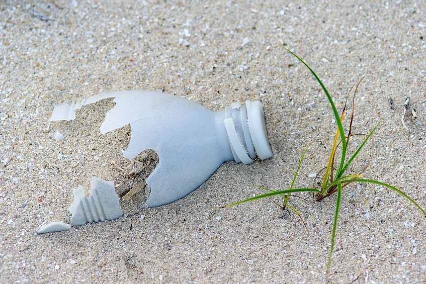 Damaged plastic bottle in sand